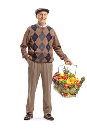 Full length portrait of an elderly man carrying a shopping basket with fruits and vegetables and posing isolated on white background Reklamní fotografie