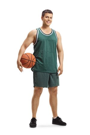 Full length portrait of a handsome basketball player in a jersey holding a ball and smiling at the camera isolated on white background