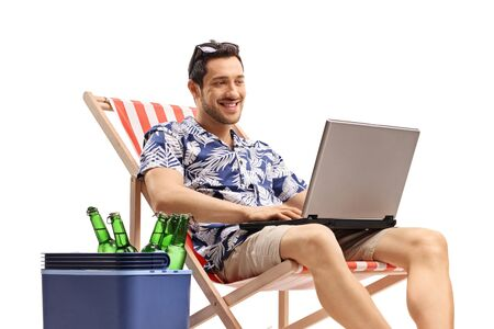 Male tourist with a laptop sitting in a deck chair next to a cooling box with beer bottles isolated on white background