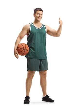 Full length portrait of a male basketball player in a jersey holding a ball and showing thumbs up isolated on white background