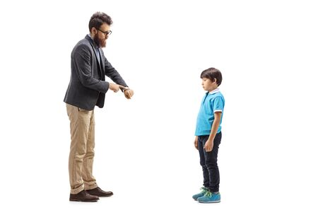 Full length shot of a father scolding his son and looking at this watch isolated on white background