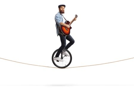 Full length shot of a young man riding a unicycle on a rope and playing an acoustic guitar isolated on white background