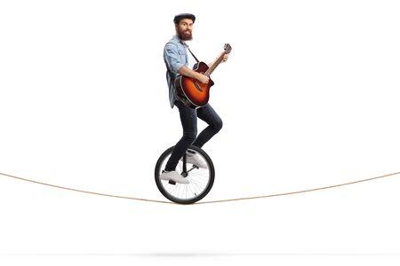 Photo de toute la longueur d'un jeune homme chevauchant un monocycle sur une corde et jouant de la guitare acoustique isolé sur fond blanc
