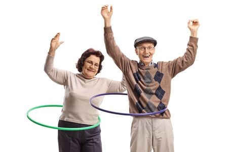 Male and female seniors with hula-hoops dancing isolated on white background Reklamní fotografie