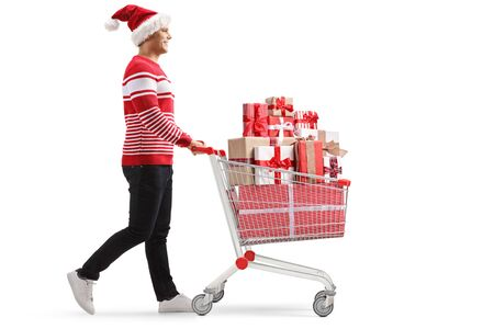 Full length profile shot of a young man with a santa claus hat pushing a shopping cart with presents isolated on white background