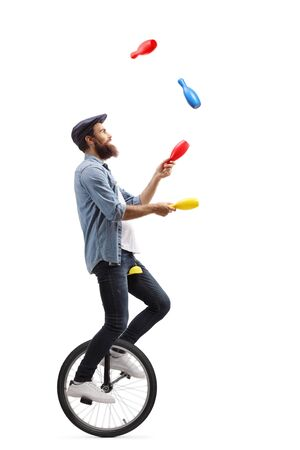 Full length profile shot of a male juggler on a unicycle juggling with clubs isolated on white background 写真素材 - 124977224