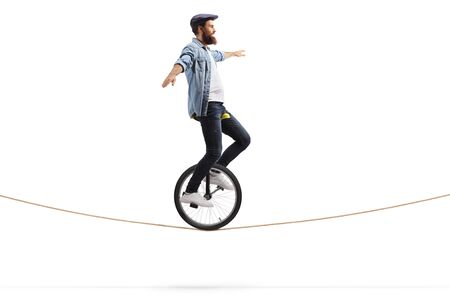 Full length shot of a young man riding a unicycle on a rope and balancing with hands isolated on white background Reklamní fotografie