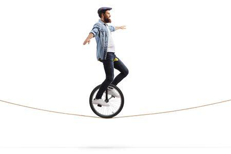 Photo de toute la longueur d'un jeune homme chevauchant un monocycle sur une corde et en équilibre avec les mains isolées sur fond blanc Banque d'images