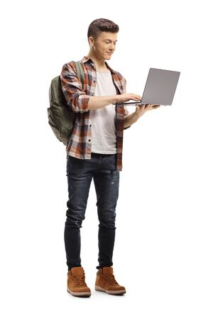 Full length portrait of a male student standing and using a laptop computer isolated on white background