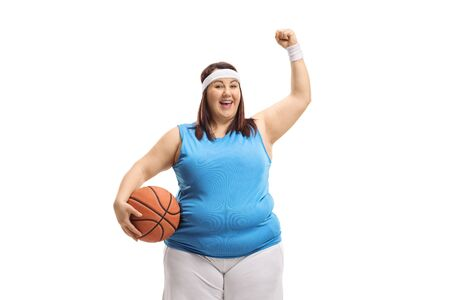 Corpulent woman holding a basketball and gesturing happiness isolated on white background