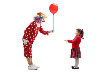 Full length shot of a clown giving a balloon to a little girl isolated on white background
