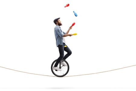 Full length profile shot of a male juggler with clubs riding a unicycle on a rope isolated on white background 免版税图像