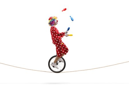 Full length profile shot of a clown juggling with clubs and riding a unicycle on a rope isolated on white background Stock fotó