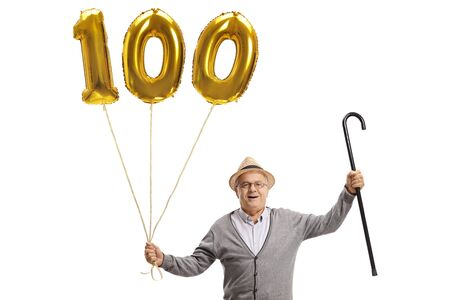 Happy senior with a golden number hundred balloon and a cane isolated on white background