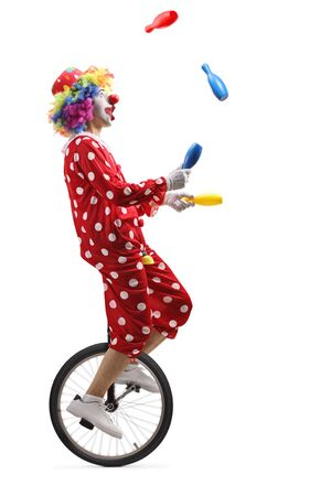 Full length profile shot of a clown on a unicycle juggling with clubs isolated on white background