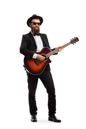 Full length portrait of a cheerful musician playing an acoustic guitar isolated on white background Stock Photo