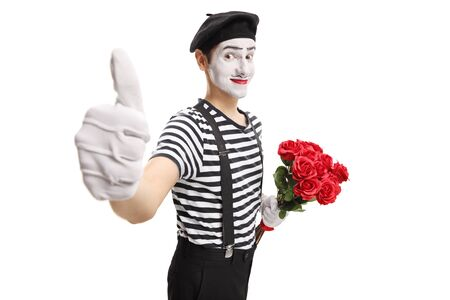 Mime holding a bunch of red roses showing thumbs up isolated on white background