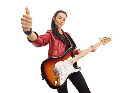 Young woman with an electric guitar showing thumbs up isolated on white background