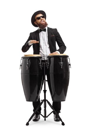 Bearded man in a suit playing conga drums isolated on white background
