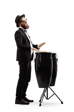 Full length shot of a man in a black suit playing conga drums isolated on white background Imagens