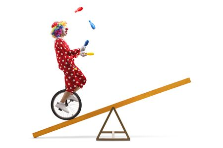 Full length shot of a clown riding a unicycle on a beam and juggling isolated on white background Imagens