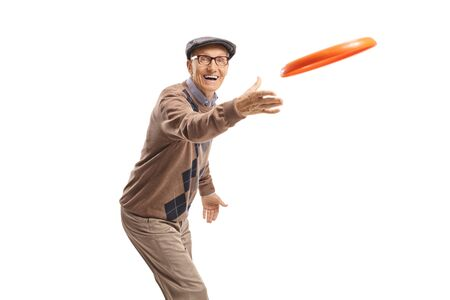 Cheerful elderly man playing with a frisbee isolated on white background