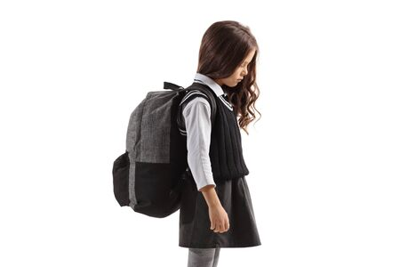 Sad little schoolgirl with a backpack isolated on white background Stockfoto