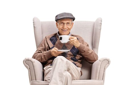Elderly man sitting in an armchair and drinking a cup of tea isolated on white background Stok Fotoğraf