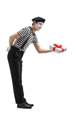 Full length shot of a mime giving a gift box isolated on white background