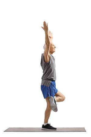 Full length shot of an older man exercising yoga on a mat isolated on white background