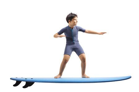 Full length shot of a boy in a wetsuit standing on a surfing board isolated on white background