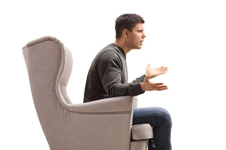 Profile of a young man sitting in an armchair and arguing with someone isolated on white background Banco de Imagens