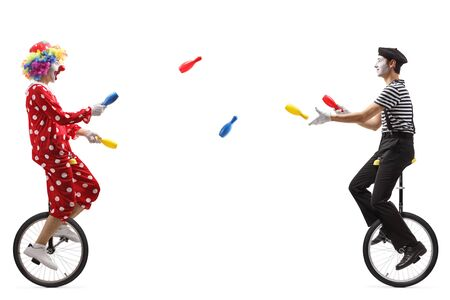 Full length profile shot of a mime and a clown on unicycles juggling with clubs isolated on white background
