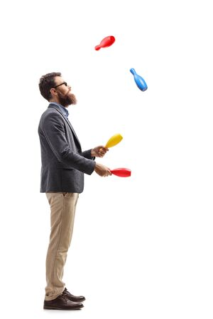 Full length profile shot of a bearded man juggling with clubs isolated on white background