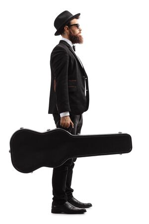 Full length profile shot of a male musician standing and holding a guitar in a black case isolated on white background