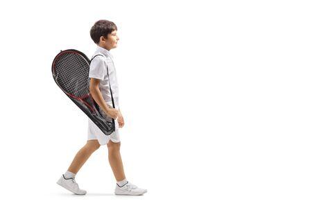 Disparo de perfil de longitud completa de un niño caminando con una raqueta de tenis en un caso aislado sobre fondo blanco.