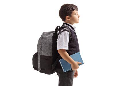 Profilansicht eines Schuljungen in Uniform und Rucksack isoliert auf weißem Hintergrund Standard-Bild