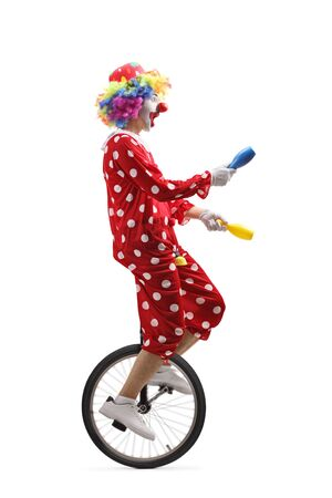 Full length profile shot of a juggler clown riding a unicycle and juggling isolated on white background