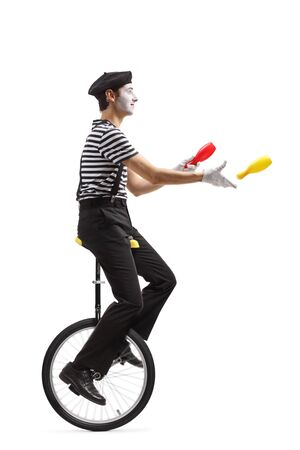 Full length profile shot of a mime juggler riding a unicycle and throwing plastic clubs isolated on white background Stock Photo