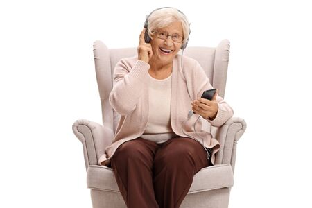 Senior woman seated in an armchair listening to music on a phone and looking at the camera isolated on white background