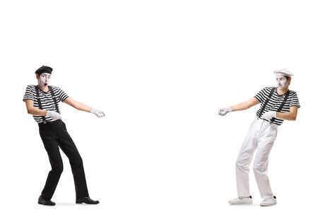 Full length shot of two pantomime men pulling an imaginary rope isolated on white background