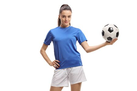Jonge vrouwenvoetballer die een voetbal houdt die op witte achtergrond wordt geïsoleerd