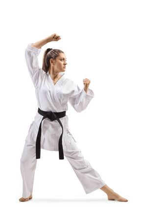Full length shot of a woman with black belt and kimono practicing karate kata isolated on white background