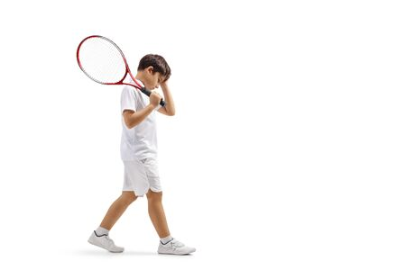 Full length profile shot of a sad boy with a tennis racquet isolated on white