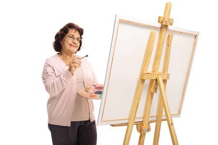 Glückliche ältere Frau mit Pinsel und Farben malen auf einer Leinwand isoliert auf weiß