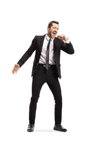 Retrato de cuerpo entero de un joven en traje cantando en un micrófono aislado sobre fondo blanco.