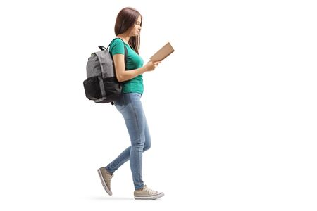 Full length profile shot of a female with a backpack reading a book and walking isolated on white background