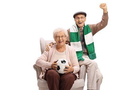 Cheerful senior man and woman soccer fans with a football and a scarf sitting in an armchair isolated on white background