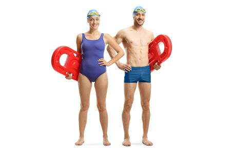 Full length portrait of a young man and woman in swimming suit holding swimming floats isolated on white background