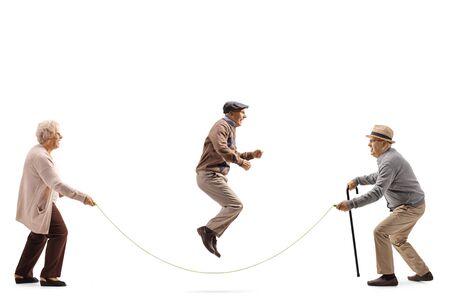 Disparo de perfil de longitud completa de personas mayores saltando una cuerda aislado sobre fondo blanco.